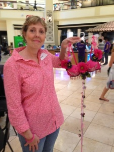 Sharon displays her contribution to the Cups of Courage breast cancer awareness exhibit